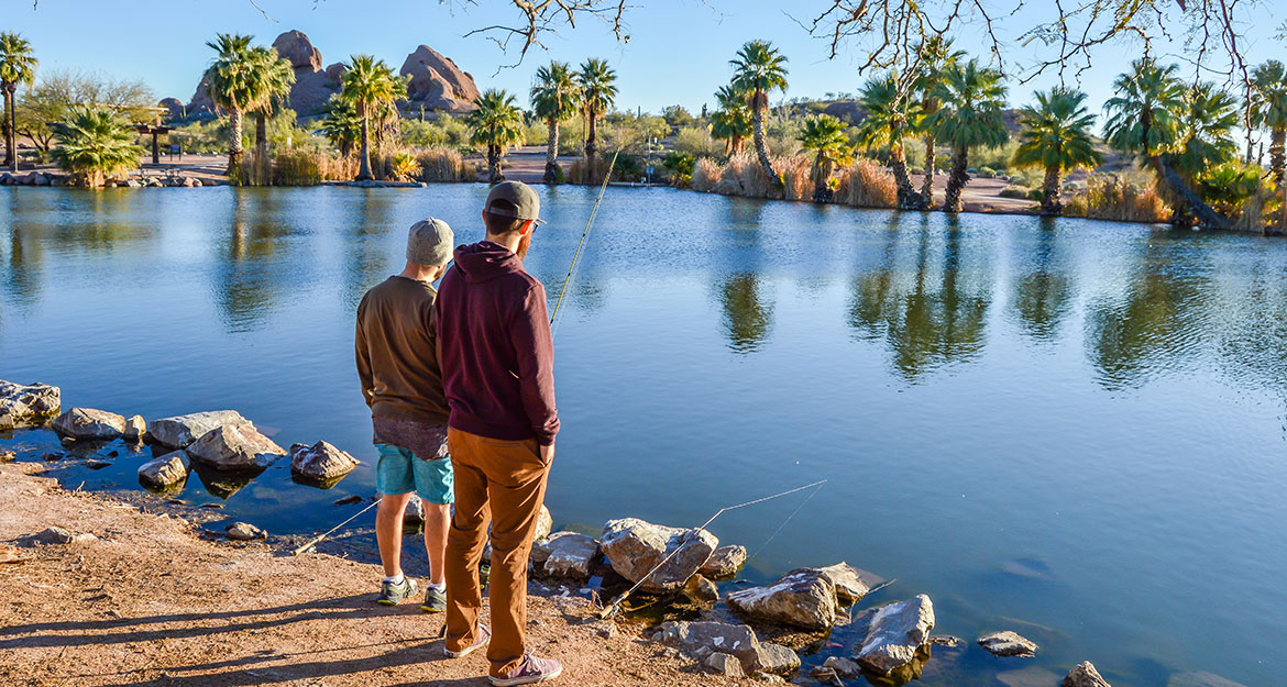 Two men stand in front of a pond ringed by palm trees, their fishing rods nearby. The caption reads: A pair of urban fisherman enjoy one of the 29 different fishing locations spread throughout the Valley of the Sun