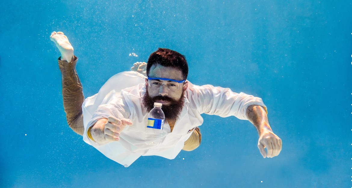 A man in a lab coat floats underwater, reaching out for a plastic bottle before him.