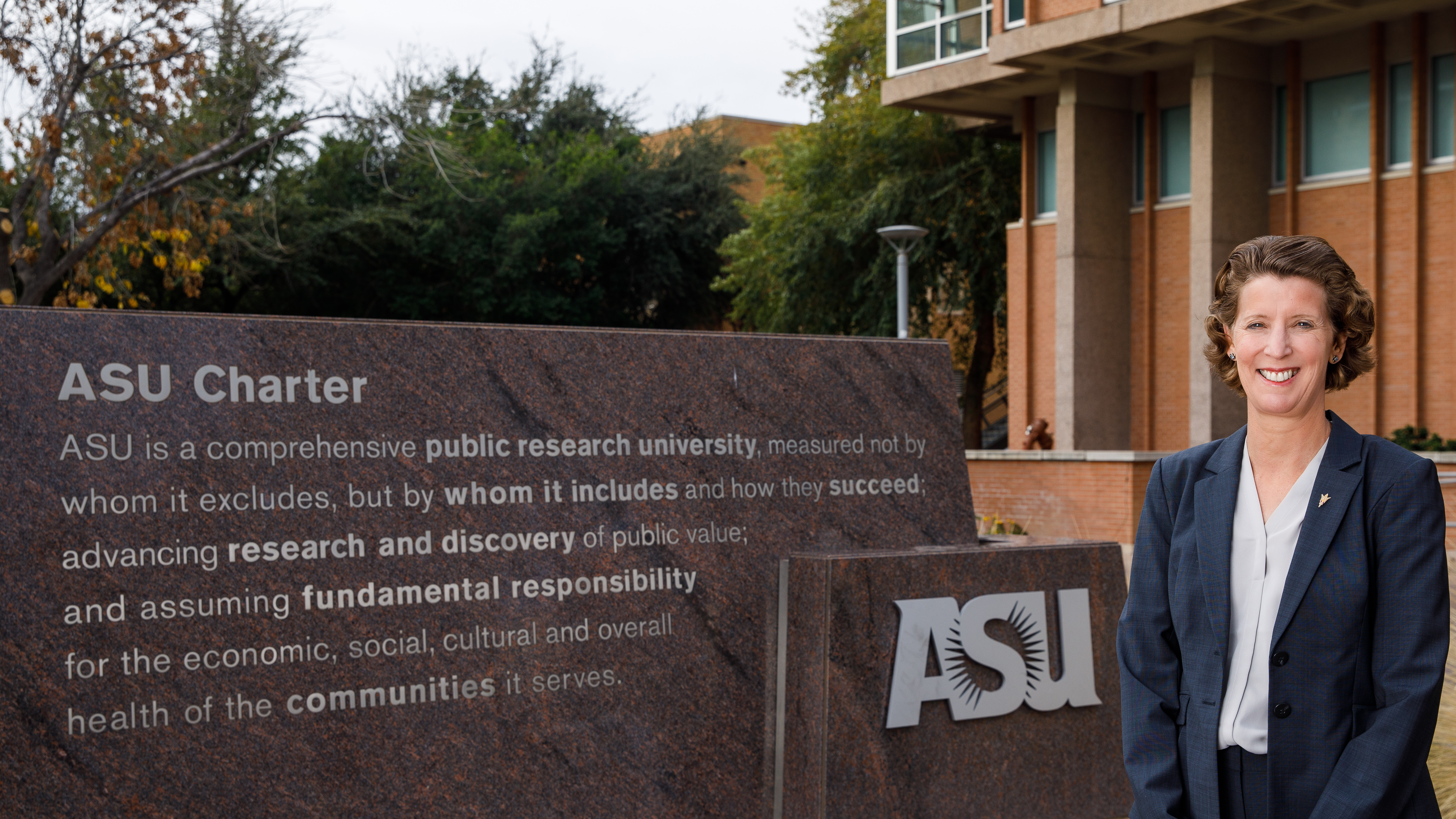 Sally C. Morton standing and smiling in front of the ASU Charter on the Tempe campus