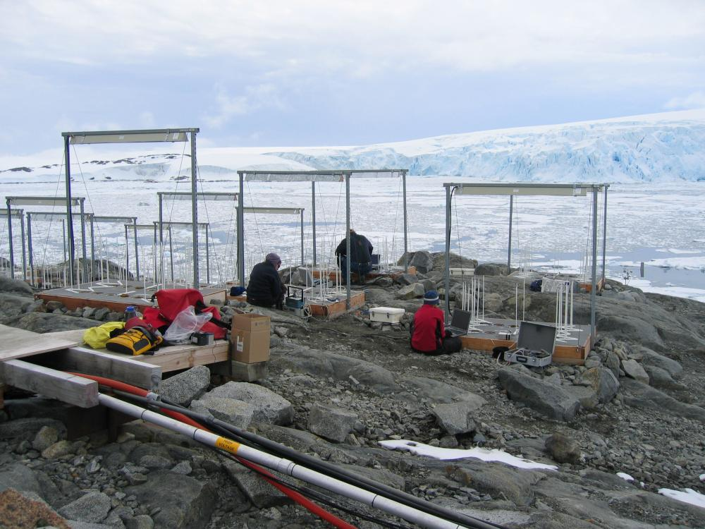 student researchers work with scaffolds along the side of a glacier