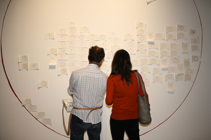 A man and women look at a wall filled with sticky notes