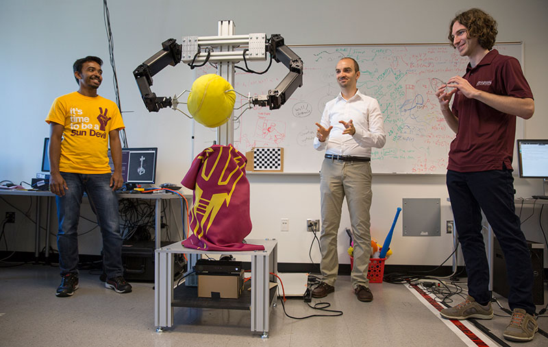 """I'm always having a blast with my students, coming up with crazy ideas,"" says Heni Ben Amor (center), shown here with Yash Rathore (left) and Kevin Luck teaching a robot to throw a ball. Photo by Jessica Hochreiter."