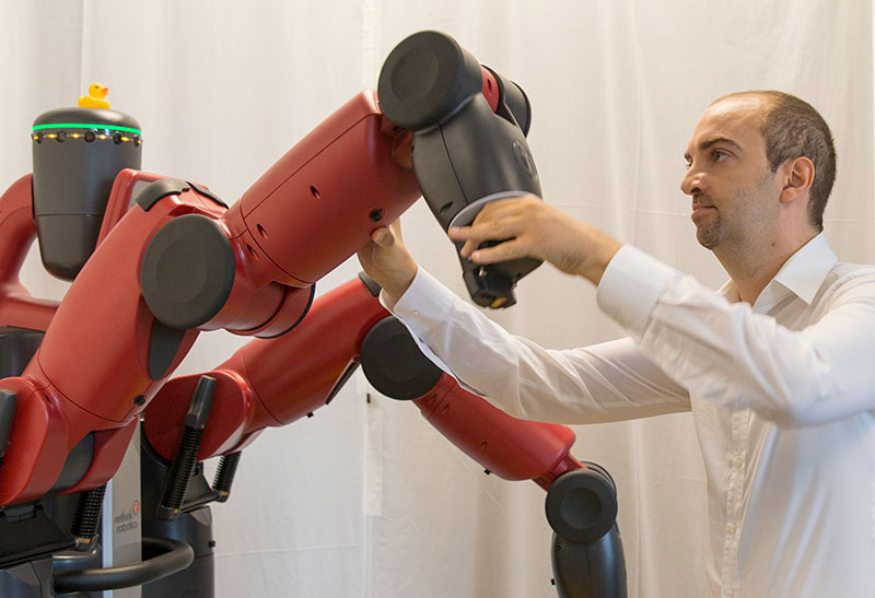 Heni Ben Amor works with a Baxter robot in his lab. Photo by Jessica Hochreiter.