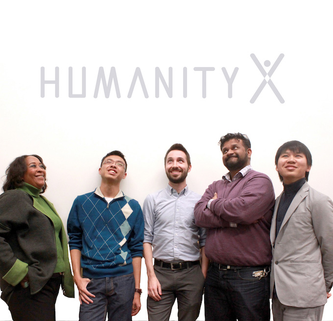 HumanityX team poses in from of a sign