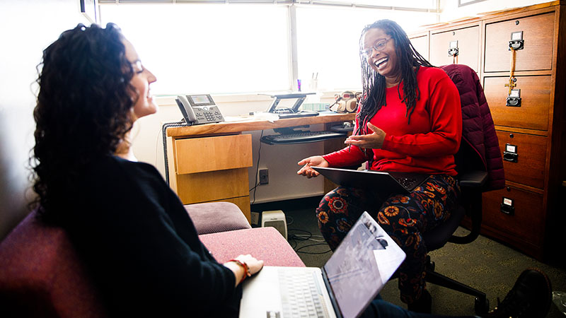 Kiki Jenkins laughs while talking to her student in her office
