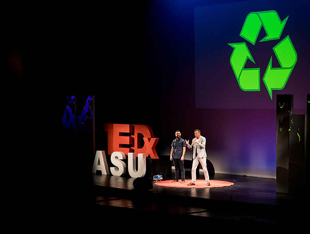 Two men stand on a brightly lit stage, giant TEDxASU letters to their right and a giant recycling icon projected behind them.