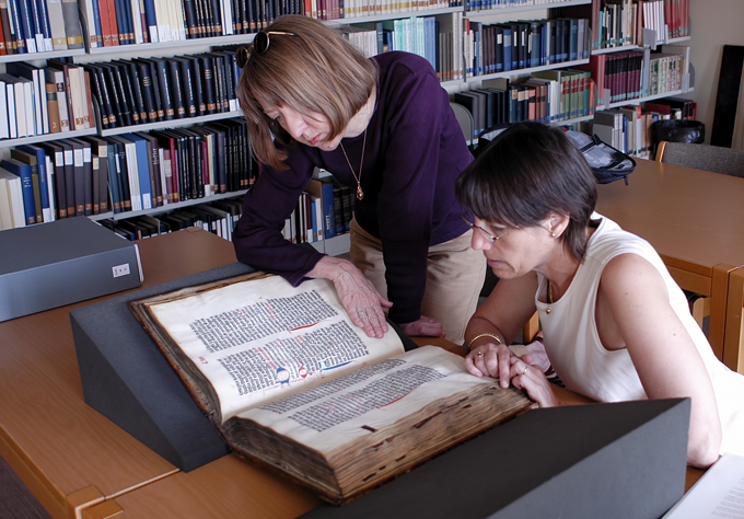 Two women stare at a big book in a library