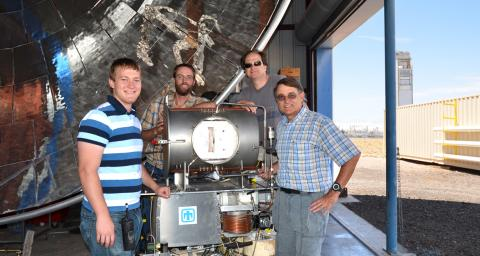 A group of men stand around a piece of scientific equipment. The caption reads: Jim Miller, second from right, with colleagues at Sandia National Laboratories and the CR5 thermochemical reactor.