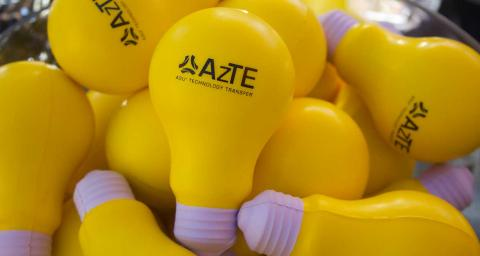 Pile of yellow lightbulbs with AzTE stamped on them