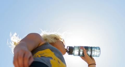 A young woman, backlight from above by the sun, drinks from a bottle of water. Photo by Andy DeLisle.