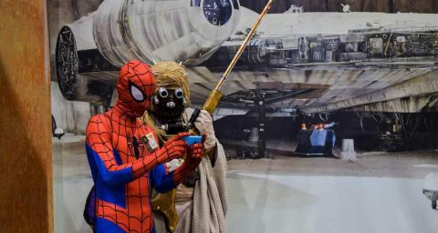 Spiderman and person from Star Wars looking at phone together