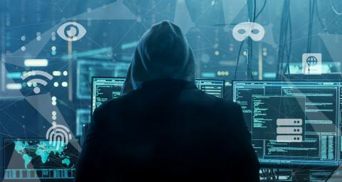 A person in a hoodie depicting a cyberattacker stands before computer screens and data.