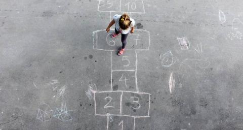 young girl jumps on a hopscotch
