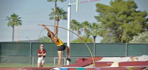 A young woman, clad in maroon and gold, pole vaults.