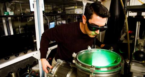 A student researcher uses safety goggles and a webcam to protect his eyes while conducting laser research.