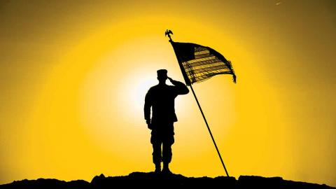 silhouette of soldier saluting U.S. flag on mountain against sunset