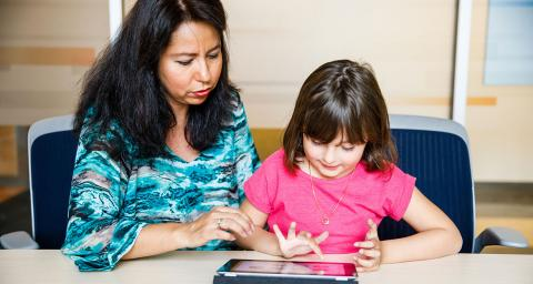 mother sits with child as child reads on ipad